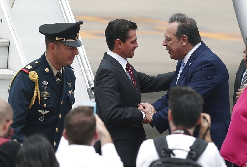 Mexico's President Enrique Pena Nieto, center, is received by Argentina's Tourism Secretary, Gustavo Santos, at the Ministro Pistarini international airport in Buenos Aires, Argentina, Thursday, Nov. 29, 2018. Leaders from the Group of 20 industrialized nations, including Pena Nieto, will meet in Buenos Aires for a two-day starting Friday.
