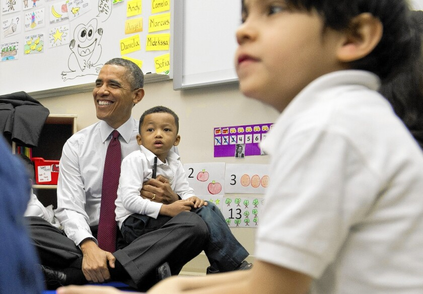 """President Obama holds Marcus Wesby during a visit to Powell Elementary School in Washington, where he promoted his spending plan for fiscal year 2015. """"Our budget is about choices. It's about our values,"""" Obama said."""