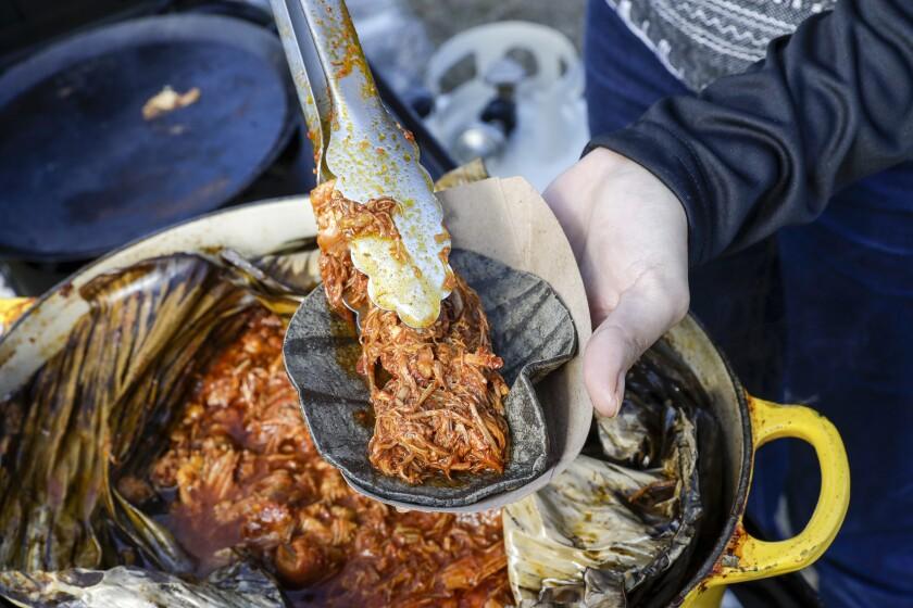 Tania Macin prepares a cochinita pibil taco at her taco stand in Echo Park.