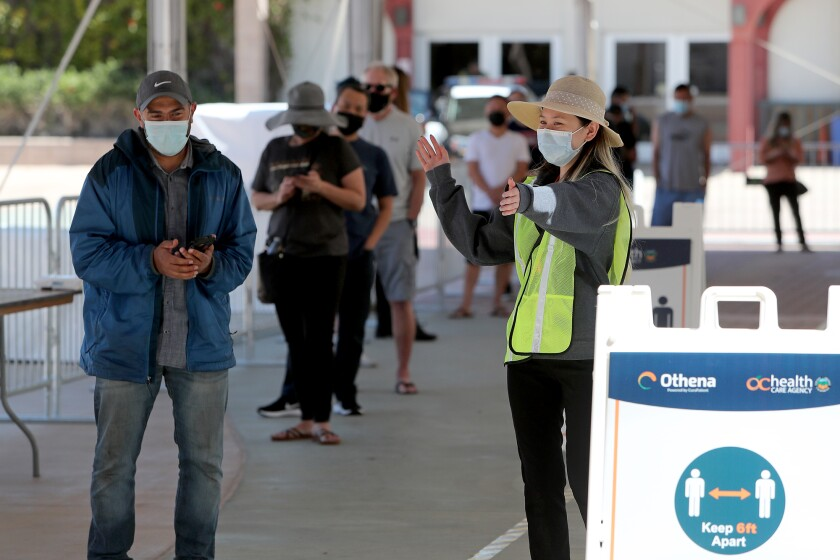 A worker directs appointment holders into the new COVID-19 vaccination super POD site at the Orange County fairgrounds.