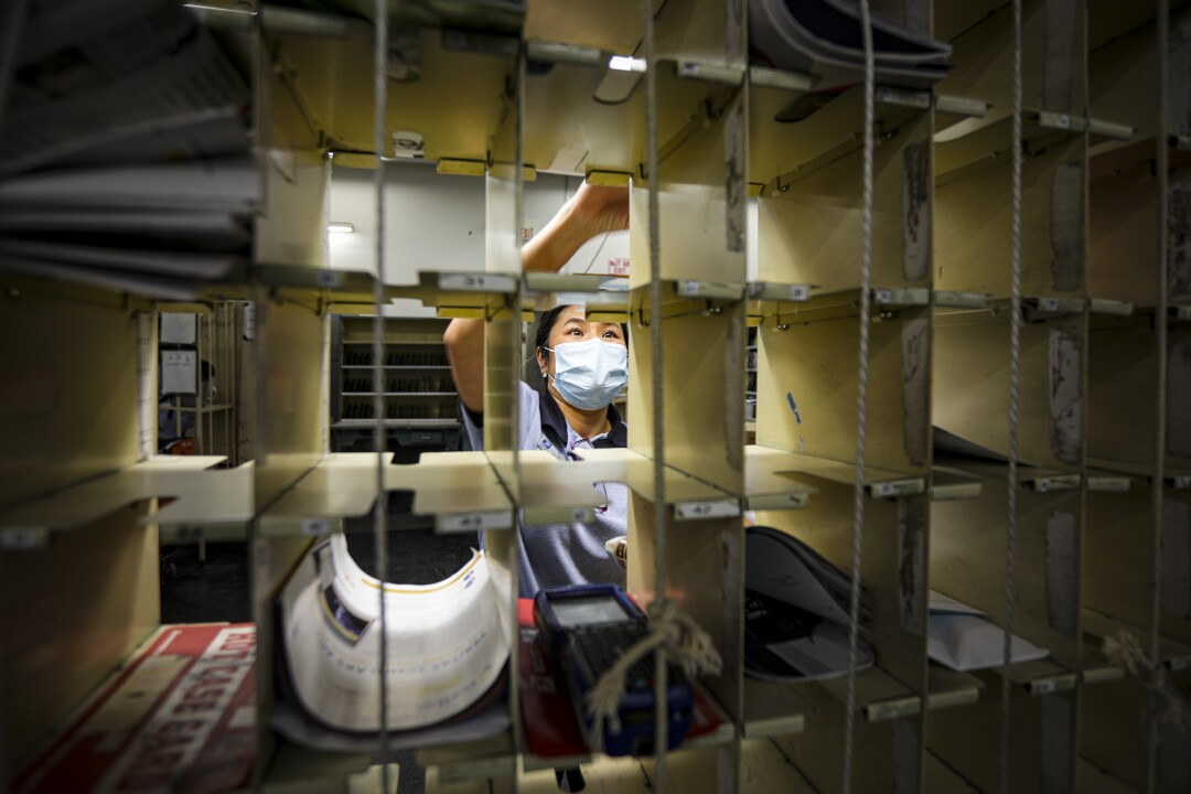 A postal worker sorts mail at a post office in San Clemente.