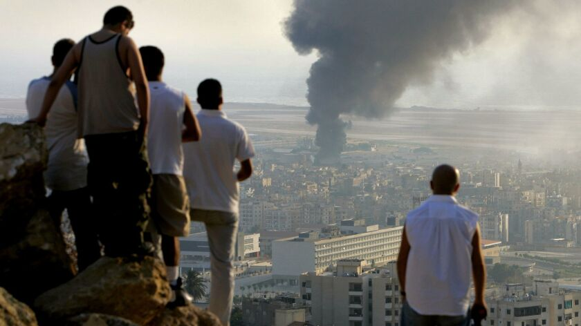 Lebanese youths gather in July 2006, during Israel's last war with Hezbollah, to watch smoke billowing after an Israeli airstrike at Beirut International Airport.