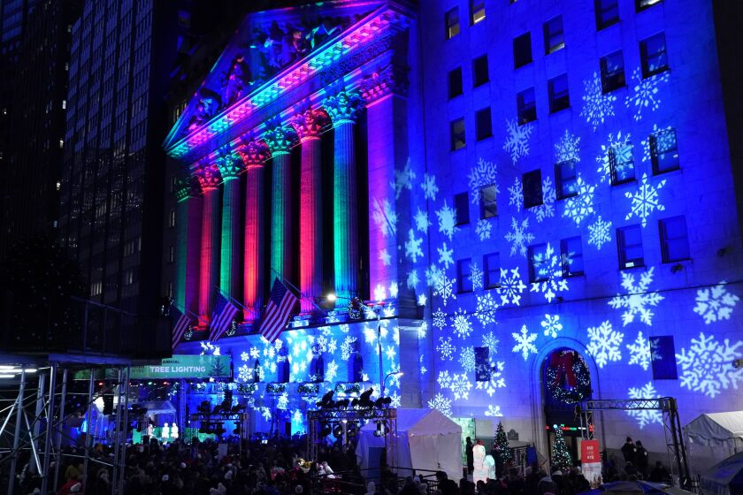 The New York Stock Exchange facade is alight in holiday colors and snowflake patterns.