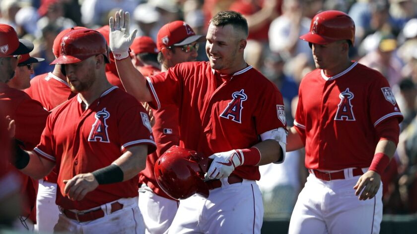 Mike Trout is congratulated by his Angels teammates after hitting a three-run home run against the Chicago Cubs on March 5.