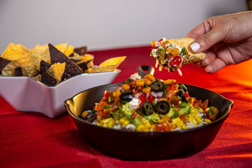 The 7-layer dip is made with beans, cheese, cream, guacamole, corn, salsa, and olives.