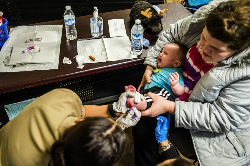 Flint resident Sheree Walker holds onto her 5-month-old son Ryder Walker as to U.S. Public Health Service health officials prick his foot with a needle, collecting blood for a free lead test on Monday, Feb. 8, 2016 at Carriage Town Ministries in Flint, Mich. Molina Healthcare provided children up t