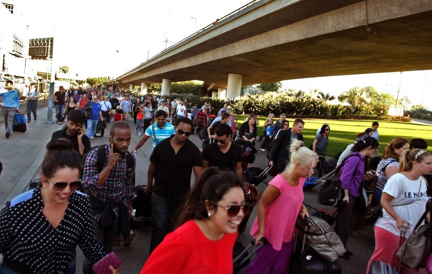 After hours of waiting, travelers stream back into LAX to make their flights, which had been delayed when a gunman began shooting inside the airport Nov. 1.