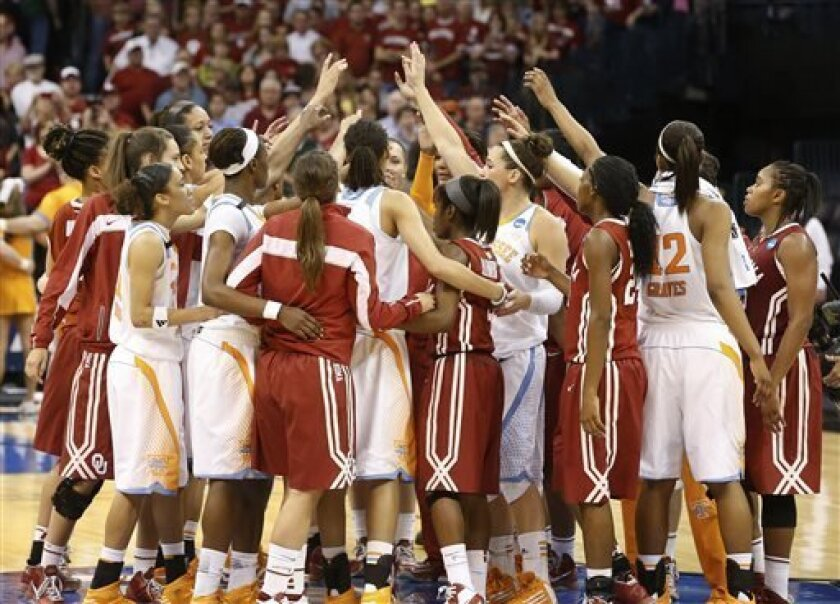 Tennessee and Oklahoma players raise their arms at mid-court following a regional semi-final game in the women's NCAA college basketball tournament in Oklahoma City, Sunday, March 31, 2013. Tennessee won 74-59. (AP Photo/Sue Ogrocki)