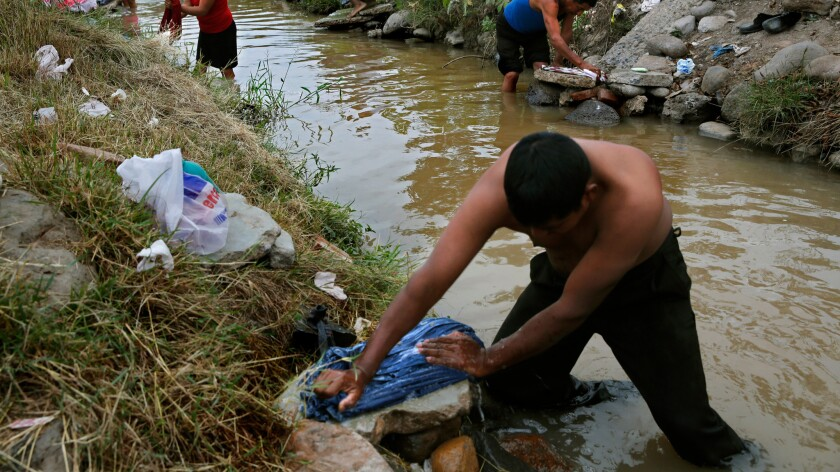 Farm laborer Luis Perez washes clothes after bathing in an irrigation canal outside Campo San Jose in the Mexican state of Sinaloa in 2013.