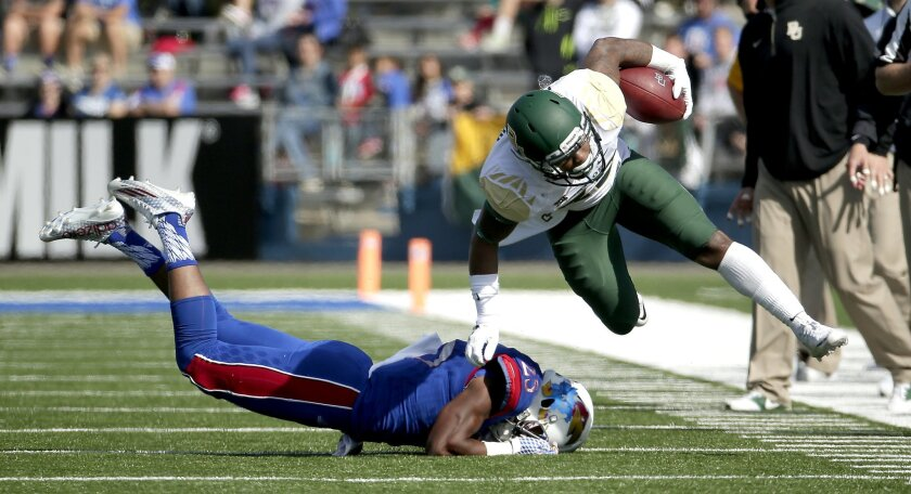 FILE- In this Oct. 10, 2015, photo, Baylor running back Shock Linwood (32) gets past Kansas cornerback Marnez Ogletree (25) as the runs the ball during the first half of an NCAA college football game in Lawrence, Kan. The College Football Playoff committee will release its first rankings of the sea