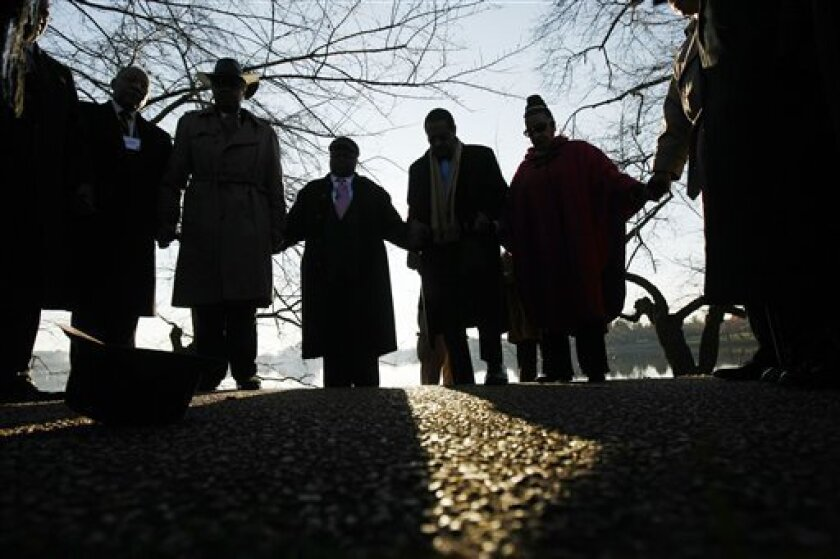 Civil rights pioneers hold hands in prayer as they arrive to survey the future site of the Martin Luther King, Jr. National Memorial in Washington, Wednesday, Dec. 3, 2008. (AP Photo/Gerald Herbert)