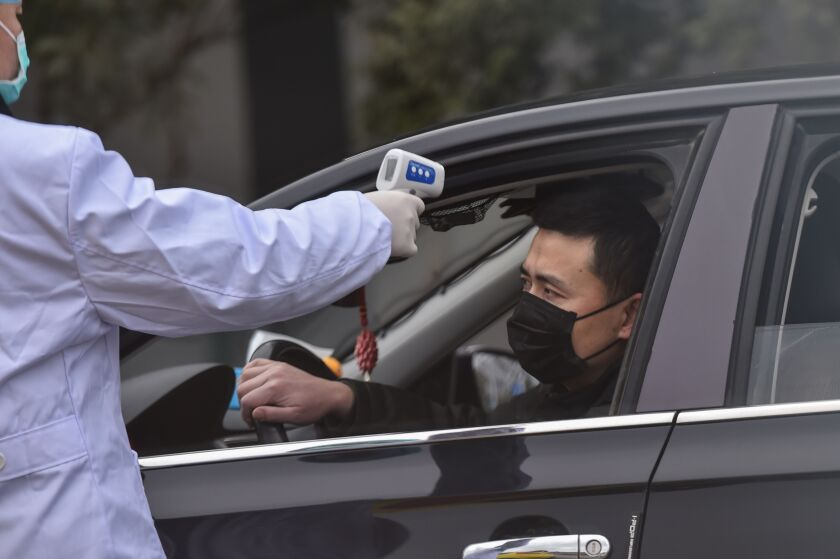 A police takes the temperature of a driver at a checkpoint on a street on the outskirts of Wuhan.
