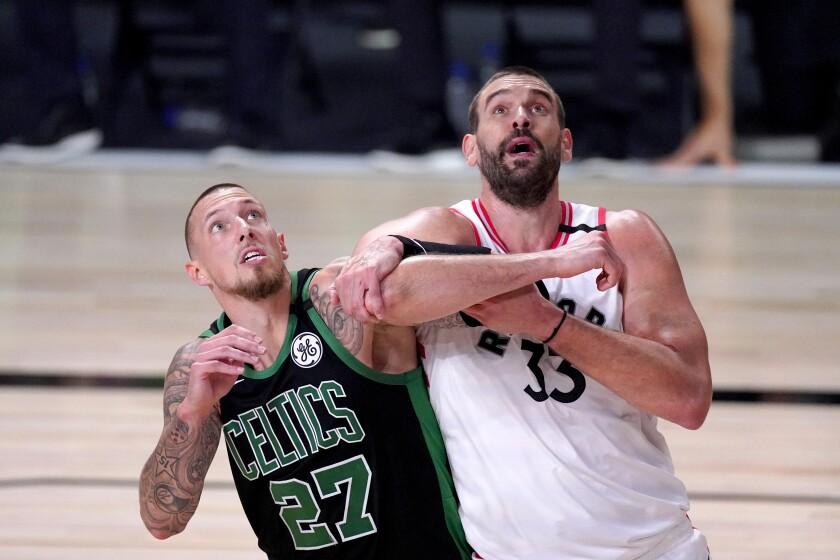 The Boston Celtics' Daniel Theis (27) and Toronto Raptors' Marc Gasol (33) struggle.