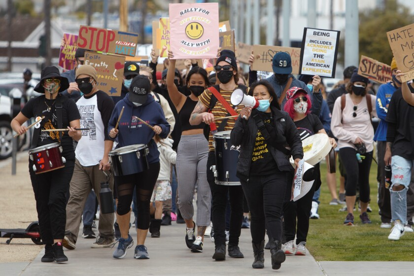 Nearly 100 people participate in a Stop Asian Hate rally, marching along Harbor Drive in San Diego on Saturday, Mar. 20.