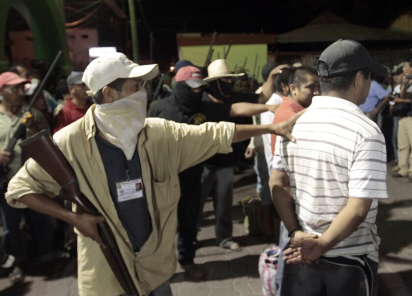 Hooded men guard the detainees at the central square of Ayutla. Hundreds of civilians armed with rifles, pistols and machetes decided to provide security for the communities of Guerrero state, creating a vigilante force, saying gangs were committing robberies, kidnappings and murder.