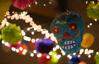 Sherman Heights, California, USA October 17th, 2019 | Inside the community center different Day of the Dead decorations hang. A large blue skeleton paper mache head hands with some lighting. Community members attend a preview night for Day of the Dead celebration at the Sherman Heights Community Center. | © Alejandro Tamayo, The San Diego Union Tribune 2019