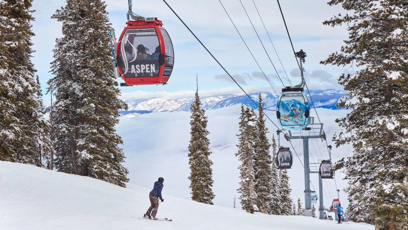 A woman skiing down a slope at Aspen Mountain with colorful gondolas overhead. Credit: Shawn O'Conno