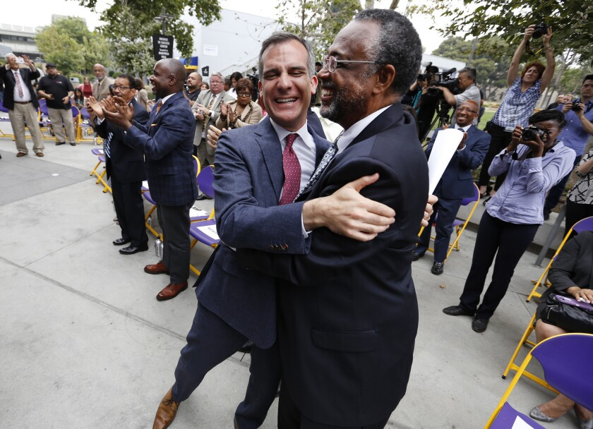 Los Angeles Mayor Eric Garcetti, left, hugs Councilman Curren D. Price, Jr., right, as Federal officials announce that South Los Angeles will be designated a promise zone.