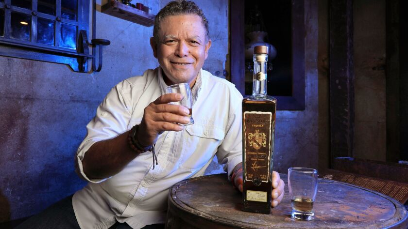 Portrait of Phillip Soto Mares with a bottle of The Bad Stuff Tequila. He is the distiller and co-founder of The Bad Stuff Spirits.