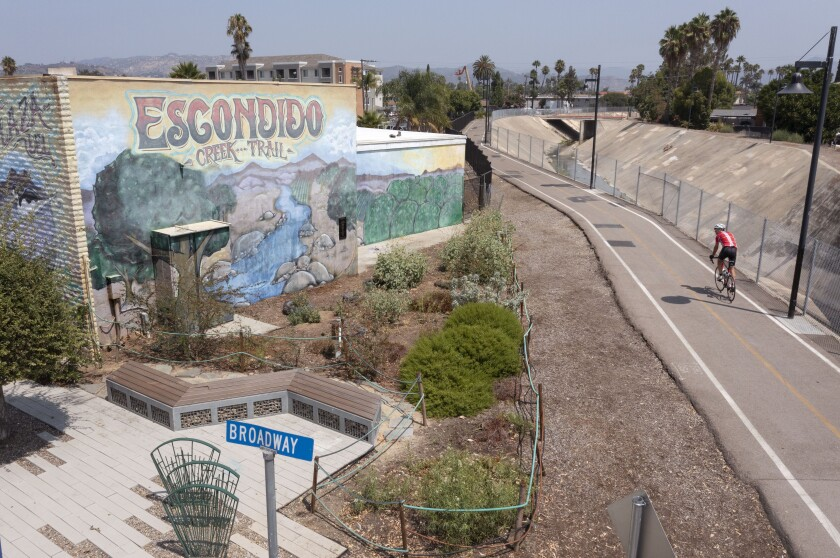 A bike rider heads east on Escondido Creek Trail bike path passes by the pocket park with its pollinator garden on Broadway
