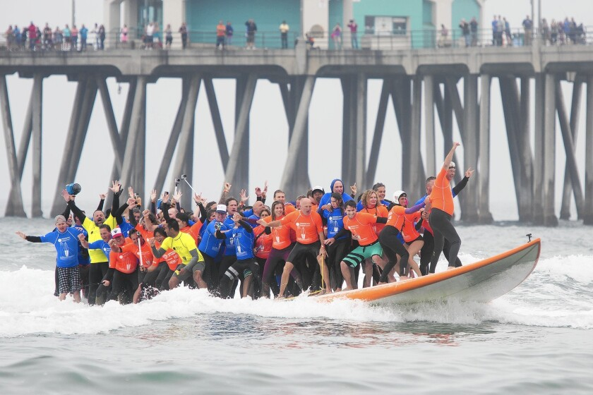 Sixty-six surfers on a record-setting 42 1/4-foot-long board set a Guinness world record for the most surfers riding a wave as they pass the Huntington Beach Pier on June 20.
