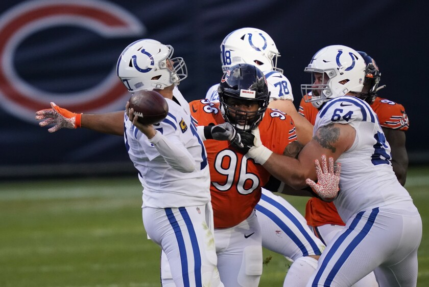 Indianapolis Colts quarterback Philip Rivers (17) throws while being pressured by Chicago Bears' Akiem Hicks (96) during the first half of an NFL football game Sunday, Oct. 4, 2020, in Chicago. (AP Photo/Charles Rex Arbogast)