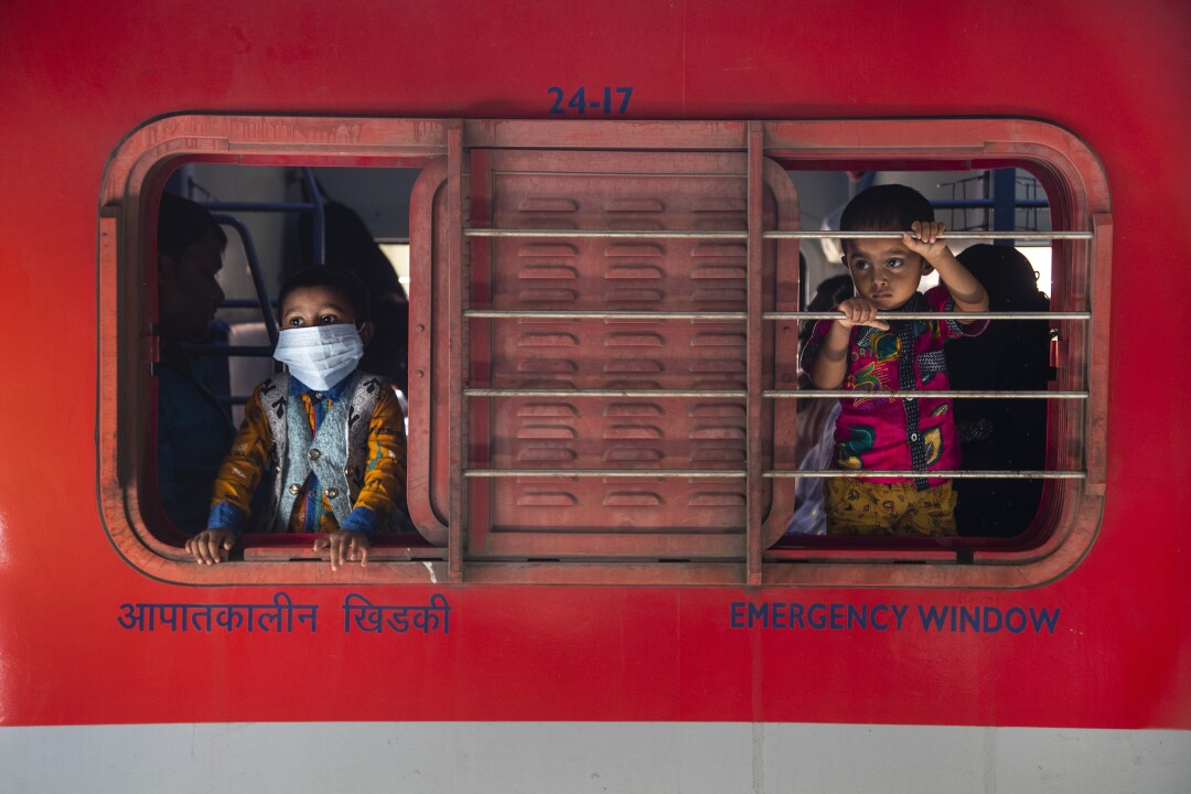 Boys look out a train window.