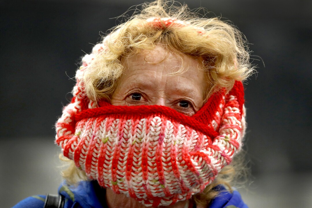 CZECH REPUBLIC: A woman covers her nose and mouth with a knitted scarf as she wait for a subway train in Prague.