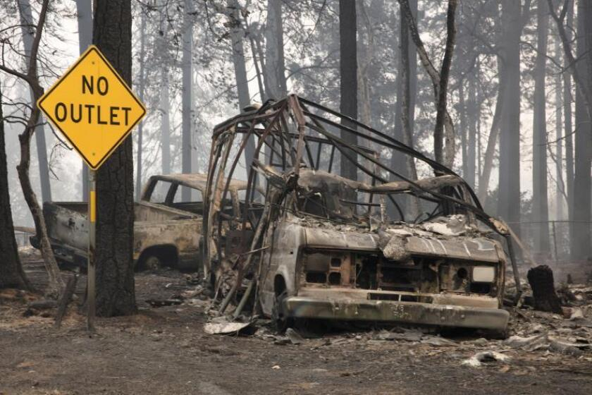 A burned out vehicle sits in the front yard of a Paradise home in the Pentz road area as the Camp Fire continues to burn through the region, fueled by high winds in Butte County, California, USA, 10 November 2018 (issued 11 November 2018). The nearby communities of Pulga, Paradise and Concow, have been ordered to evacuate the area. EPA-EFE/PETER DASILVA