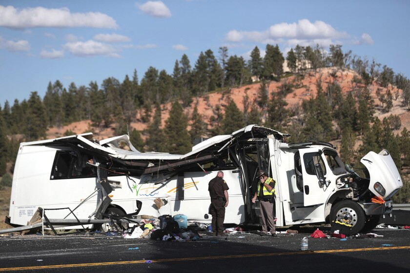 FILE - In this Sept. 20, 2019, file photo, authorities work the scene where at least four people were killed in a tour bus crash near Bryce Canyon National Park in Utah. U.S. authorities investigating a tour bus crash that killed four Chinese tourists in Utah say they haven't uncovered any mechanical problems that could have caused the September accident. The National Transportation Safety Board said Thursday, Nov. 7, 2019, the 60-year-old driver was on his first run for a new company, but he knew the area from trips with another agency. (Spenser Heaps/The Deseret News via AP, File)