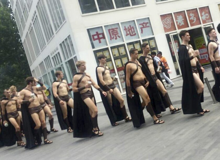 In this Wednesday, July 22, 2015, photo, men dressed in Spartan-style costumes walk through a commercial plaza in Beijing. A salad store paraded dozens of half-naked Western men dressed as Spartans through China's capital as a publicity stunt, causing a stir and drawing a crackdown by police who were photographed restraining some of them on the ground. (Photo via AP)