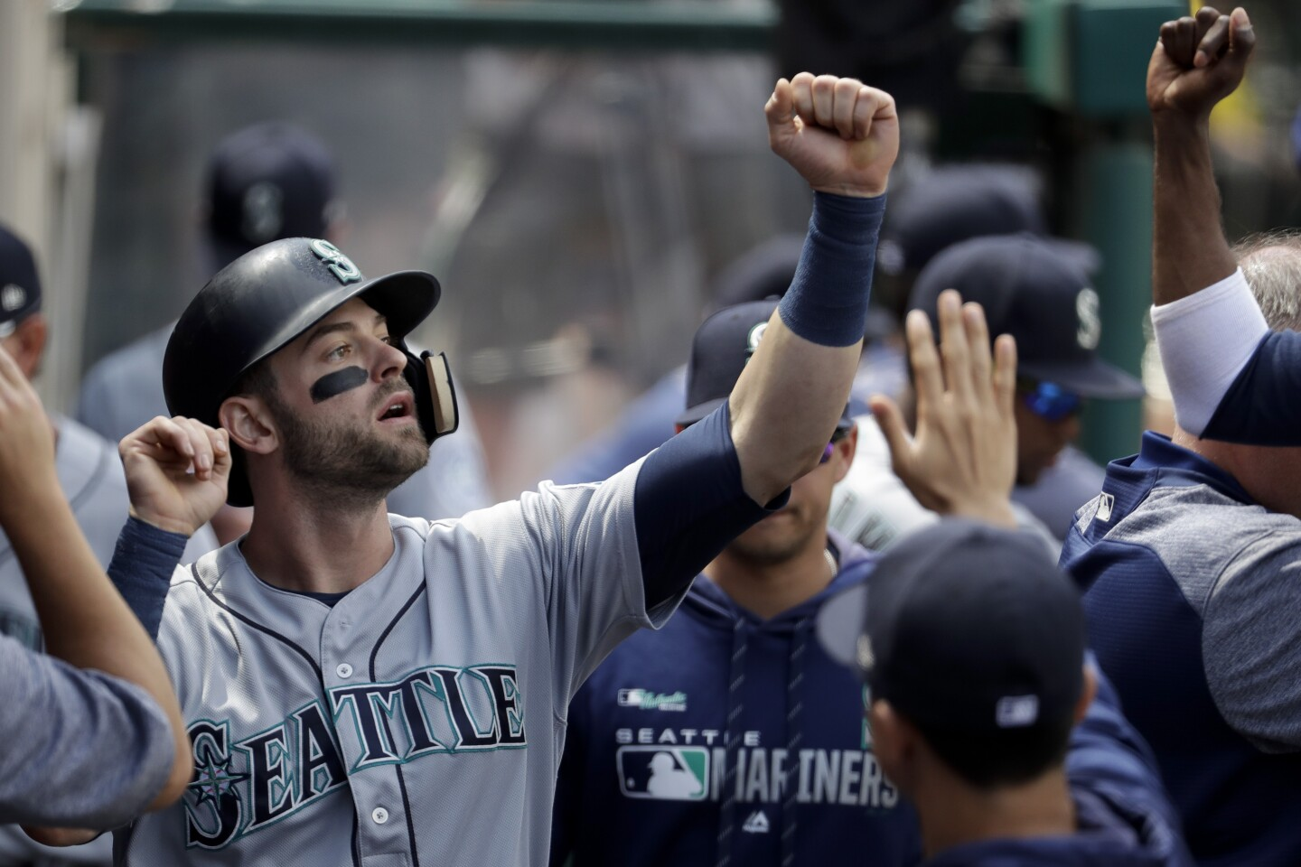 The Mariners' Mitch Haniger celebrates in the dugout after scoring on single during the third inning of a baseball game against the Los Angeles Angels in Anaheim, Calif., Sunday, April 21, 2019. (AP Photo/Chris Carlson)