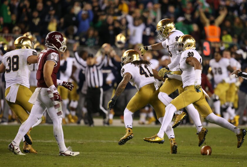 Temple's John Christopher walks away as Notre Dame celebrates an interception late in the fourth quarter of an NCAA college football game Saturday, Oct. 31, 2015, in Philadelphia. Notre Dame won 24-20. (David Maialetti/The Philadelphia Inquirer via AP)