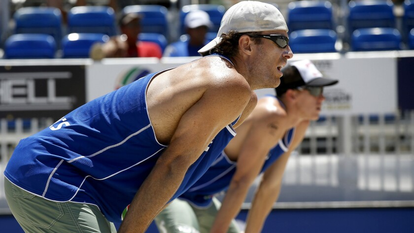John Hyden, left, and teammate Tri Bourne wait to receive a serve during the World Series of Beach Volleyball tournament in July.