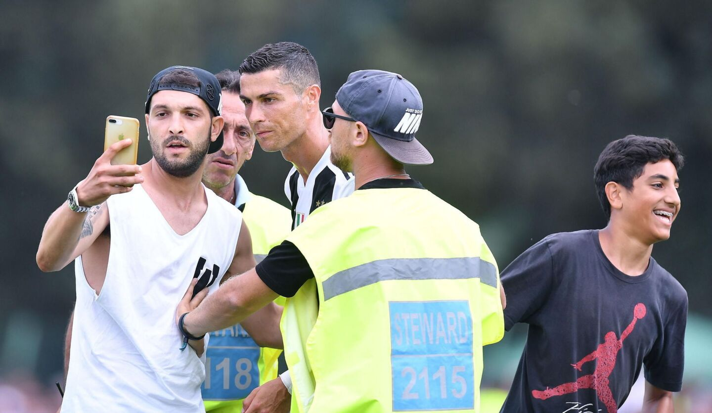 Juventus' Cristiano Ronaldo (C) with a pitch invader during a soccer friendly match between Juvents A and Juventus B at Villar Perosa, Turin, 12 August 2018.