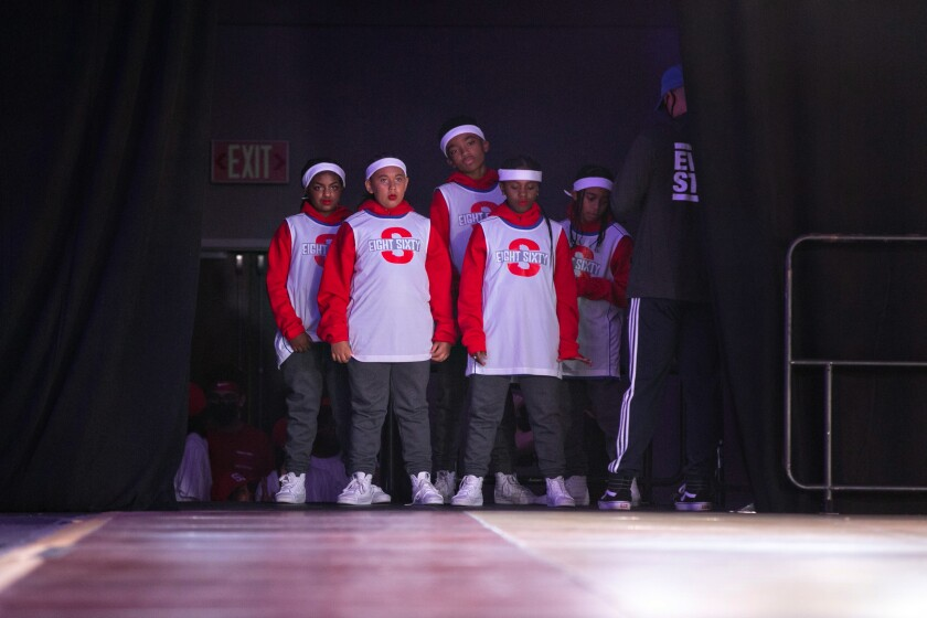 A group of five young people waits in the wings to perform.