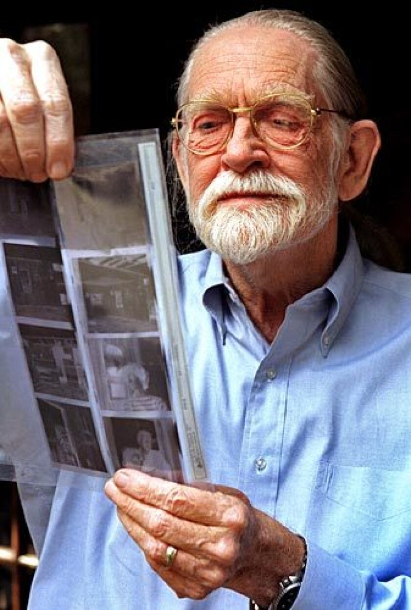 Charles Brittin examines the negatives for some of the photographs in his first solo exhibition since 1952. See full story