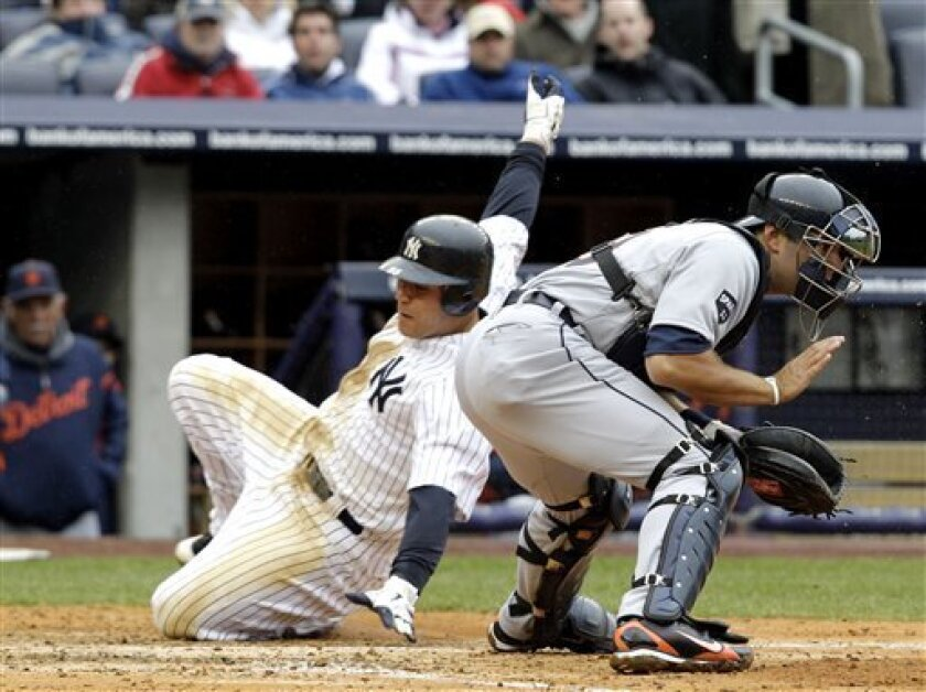 New York Yankees catcher Russell Martin slides safely past Detroit Tigers catcher Alex Avila on Derek Jeter's seventh-inning sacrifice fly in their opening day baseball game at Yankee Stadium on Thursday, March 31, 2011 in New York. (AP Photo/Kathy Willens)