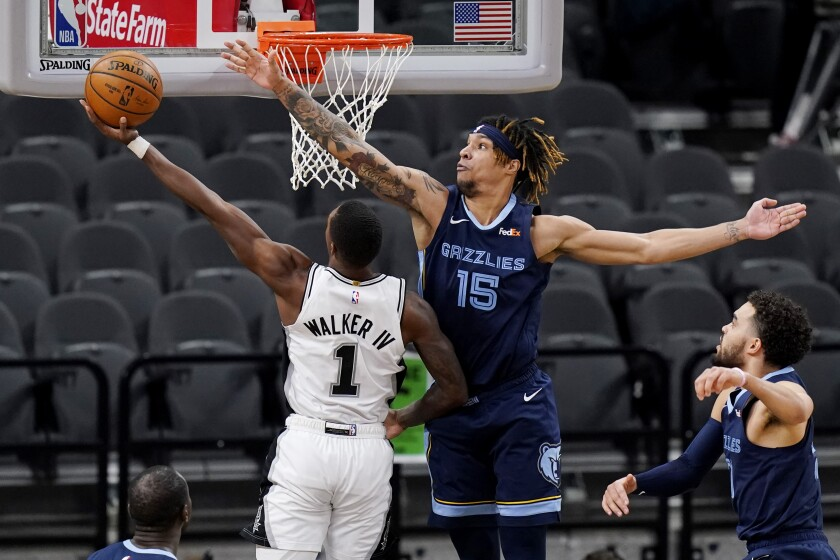 San Antonio Spurs guard Lonnie Walker IV (1) is defended by Memphis Grizzlies forward Brandon Clarke (15) as he tries to score during the first half of an NBA basketball game in San Antonio, Monday, Feb. 1, 2021. (AP Photo/Eric Gay)