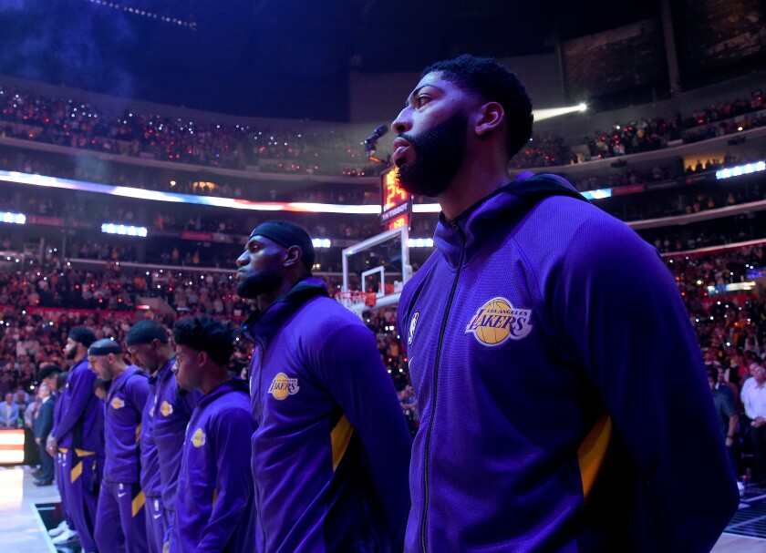 Lakers forwards Anthony Davis, right, and LeBron James listen to the national anthem before a game against the Clippers.