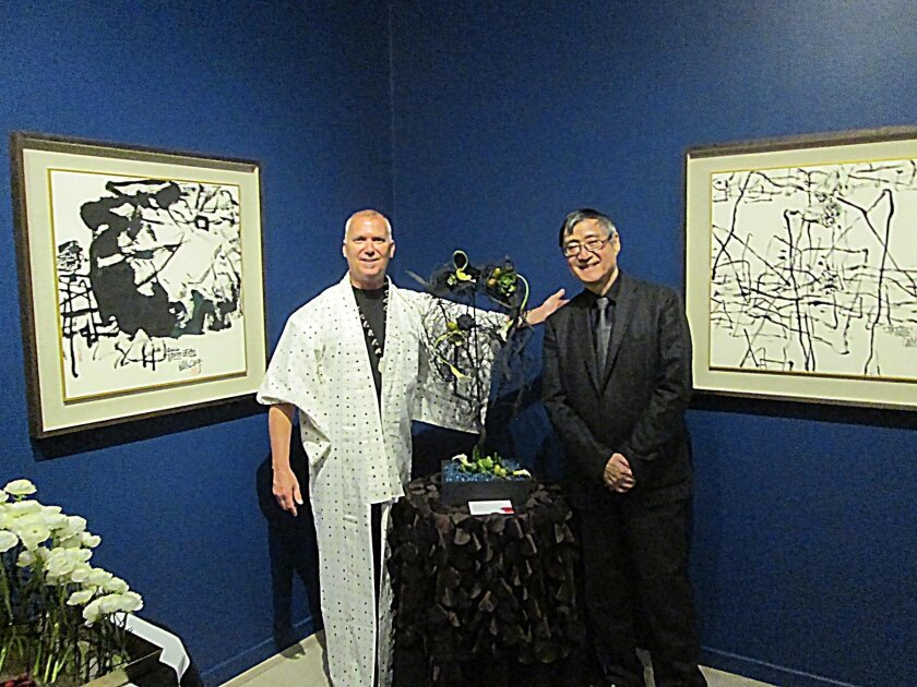 Inside, David Root poses with his interpretation of Pan Gongkai's brush and ink painting 'Lotus Pond' and Pan Gongkai. 'In my 25 years at Art Alive, this is the first time I got to meet a living artist!' Root said.