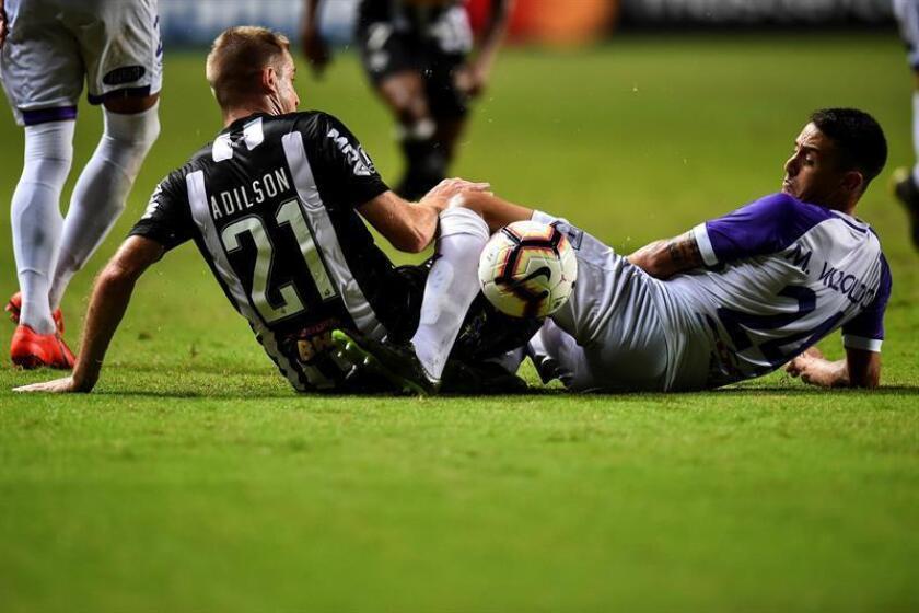 El jugador Adilson del Atlético Mineiro (i) disputa el balón con Alejandro Villoldo de Defensor Sporting (d), este miércoles, en un partido de clasificación para la fase de grupos de la Copa Libertadores de 2019, en el estadio Raimundo Sampaio de Belo Horizonte (Brasil). EFE