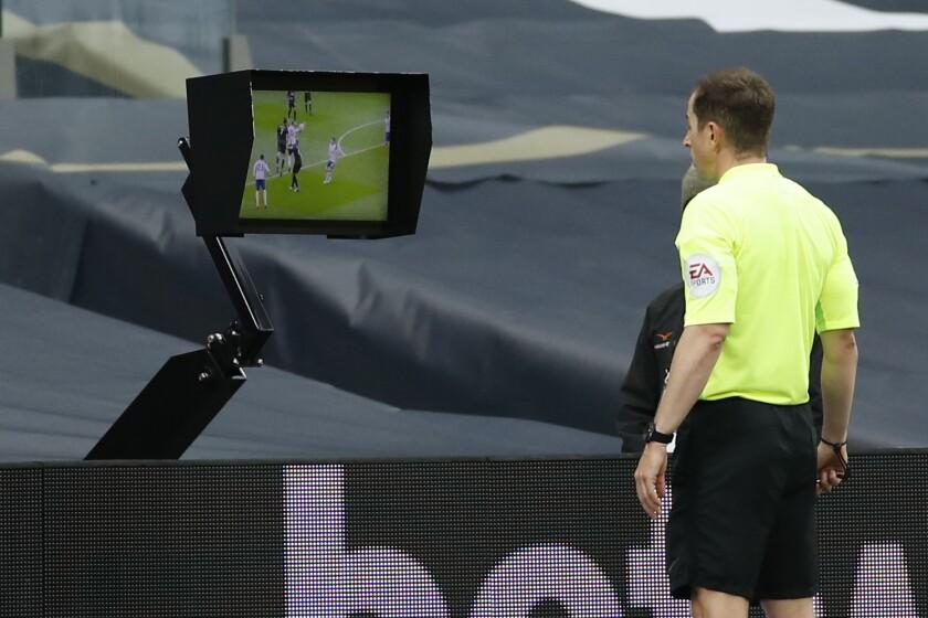 El árbitro Peter Bankes observa un monitor durante el partido Newcastle-Tottenham por la Liga Premier inglesa, el domingo 27 de septimbre de 2020, en Londres. (Andrew Boyers/Pool vía AP)
