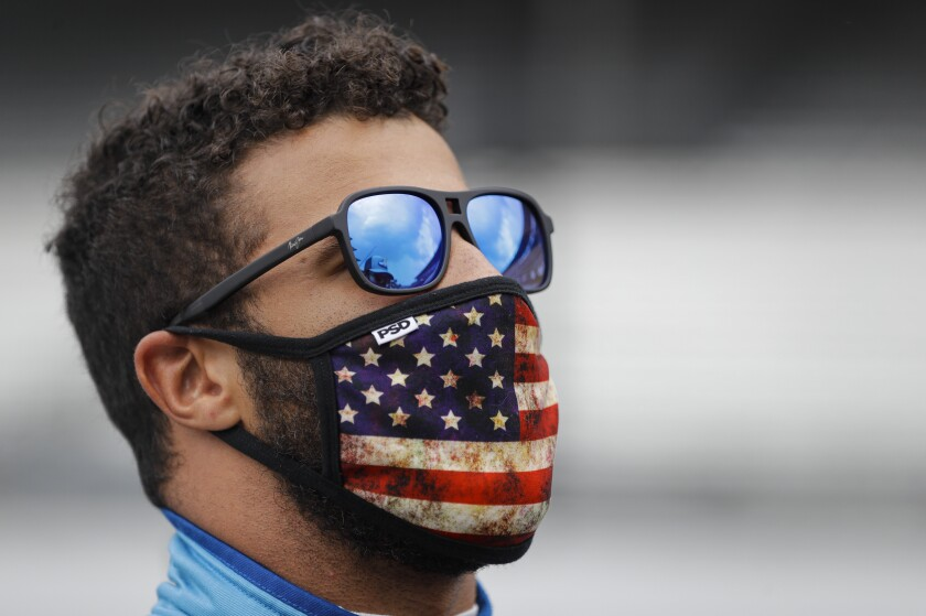 Bubba Wallace checks the sky during a weather delay before a NASCAR Cup Series race Sunday in Indianapolis.