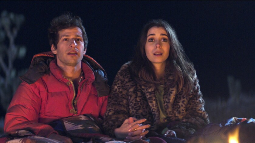 "This image released by Hulu shows Andy Samberg, left, and Cristin Milioti in a scene from the film ""Palm Springs."" (Hulu via AP)"