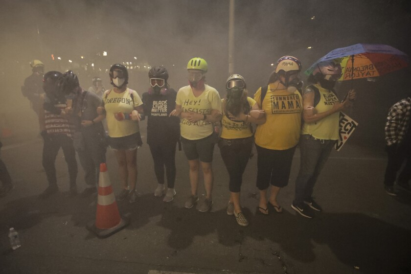 """Members of the """"Wall of Moms"""" protest group are tear-gassed by federal officers in Portland, Ore., on Monday."""