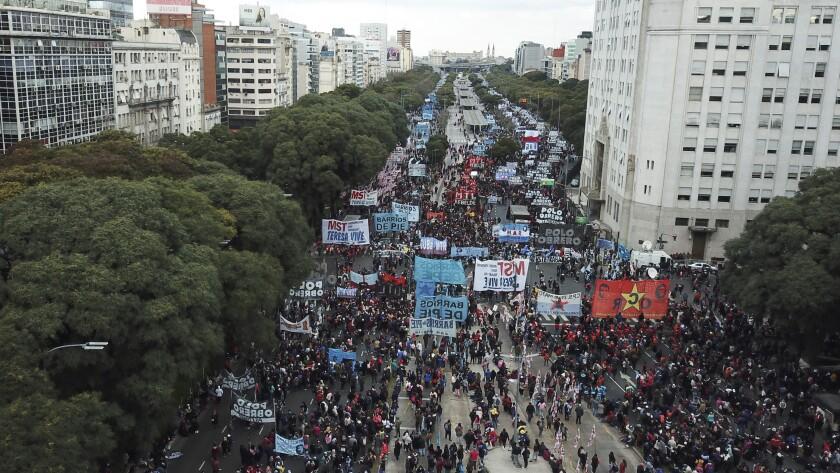 La gente marcha por la Avenida 9 de Julio para exigir mejores salarios y empleos, en Buenos Aires, Argentina, el viernes 18 de junio de 2021. (AP Foto/Víctor R. Caivano)