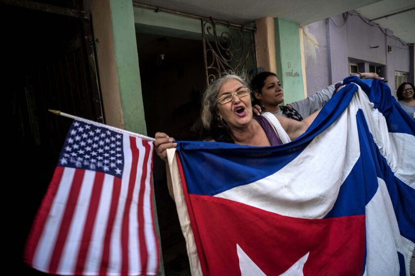"""Maria Castro shouts slogans celebrating the visit by U.S. President Barack Obama and the reconciliation of the Cuban and American peoples, while holding a Cuban and an American flag, near the Grand Theater of Havana, where President Obama delivered a speech, in Havana, Cuba,Tuesday, March 22, 2016. In his speech President Obama urged Cubans to look to the future with hope, casting his historic visit to the island nation as a moment to """"bury the last remnants of the Cold War in the Americas."""" (AP Photo/Ramon Espinosa)"""