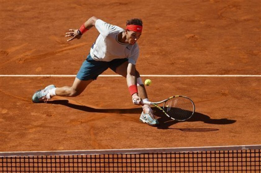 Rafael Nadal from Spain returns the ball to David Ferrer from Spain during the Madrid Open tennis tournament, in Madrid Friday, May 10, 2013. (AP Photo/Daniel Ochoa de Olza)