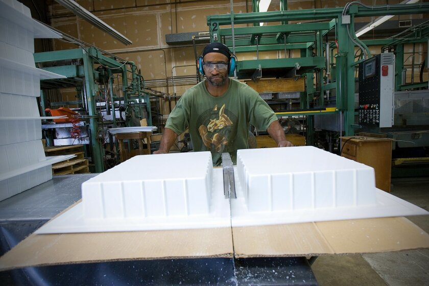 Vincent Tucker sawed two plastic trays manufactured at American Design in Chula Vista. The company's annual insurance premium has climbed from $2,200 to $4,400 in three years. (Nelvin C. Cepeda / Union-Tribune)
